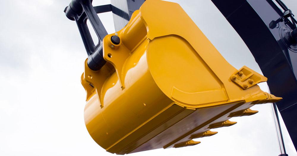Желтый ковш экскаватора-погрузчика